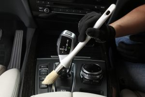 Car service: Worker Cleaning of interior by a soft brush.